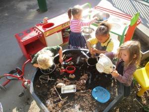Busy children learning through play outside.